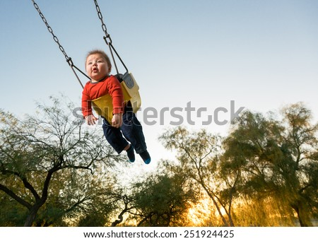Action Shot of Baby on Playground Swing Against the Sky. - stock photo