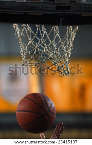 Action shot of basketball going through basketball hoop