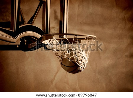 Action shot of basketball going through basketball hoop and net - stock photo
