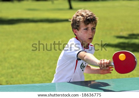 action shot of boy playing table tennis - stock photo