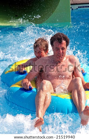 action shot of father and son at water park - stock photo