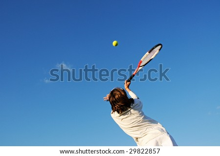 action shot of girl hitting tennis ball - stock photo