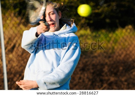 action shot of girl playing tennis - stock photo