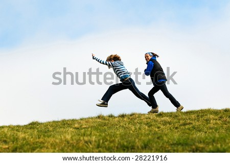 action shot of girls running along top of hill - stock photo