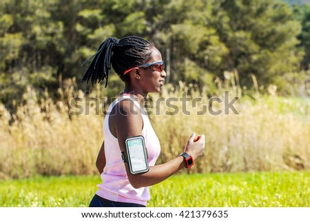 Action shot of young african woman jogging with smart watch and smart phone. Attractive teen tracking activity with fitness application. - stock photo