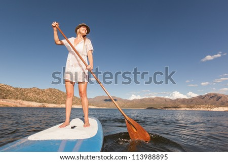 Action Shot of Young Woman on Stand Up Paddle - stock photo