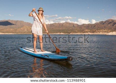 Action Shot of Young Woman Paddleboarding - stock photo