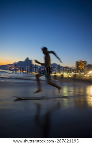 Action silhouette of Brazilian jumping onto skimboard on Ipanema Beach Rio de Janeiro Brazil at sunset - stock photo