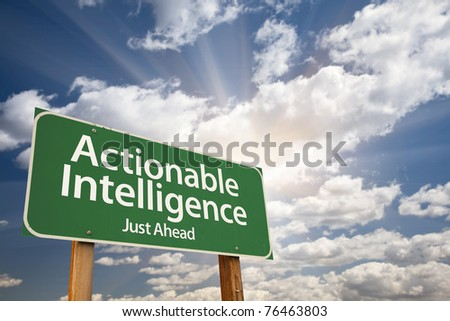 Actionable Intelligence Green Road Sign on Dramatic Blue Sky with Clouds. - stock photo