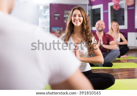 Active adults having yoga class in sport club - stock photo