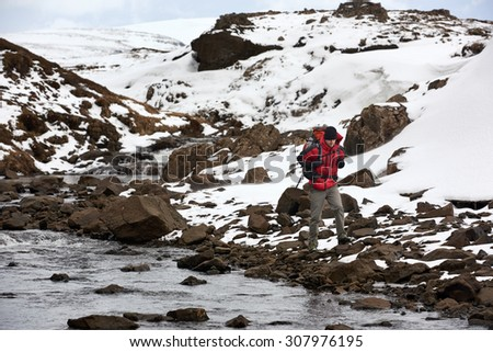 Active adventurous hiking man trekking by the river, cold winter landscape snowy icy wilderness - stock photo