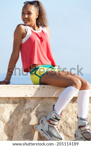 Active african american black teenager girl sitting relaxing with her roller skates by the beach, smiling during a summer sunny day on vacation, outdoors. Attractive joyful girl against a blue sky. - stock photo
