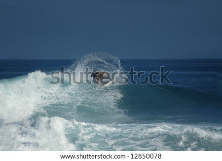 Active and athletic surfer swings his board to the music of the surf.  Blue sky and ocean. - stock photo