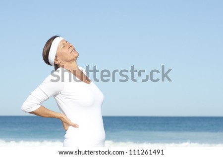 Active and attractive looking senior woman  suffering back pain, isolated with blue sky and ocean as background and copy space. - stock photo