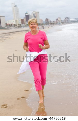 Active and happy senior woman running on beach for exercise - stock photo