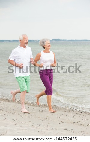 Active and sporty senior couple at the beach - stock photo