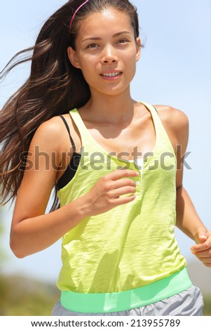 Active asian female runner running woman closeup. Chinese girl jogging portrait. - stock photo