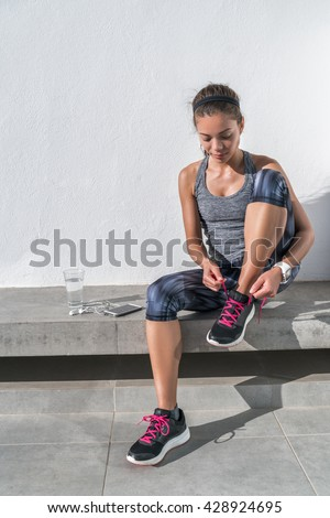 Active Asian woman getting ready for run tying running shoes on outdoor bench with smartphone, earphones earbuds and a glass of water. Athlete sporty runner in activewear living a healhty lifestyle. - stock photo