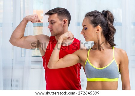 Active athletic sportive woman girl and man showing their muscles biceps healthy lifestyle. - stock photo