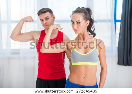 Active athletic sportive woman girl and man showing their muscles biceps healthy lifestyle looking at camera. - stock photo