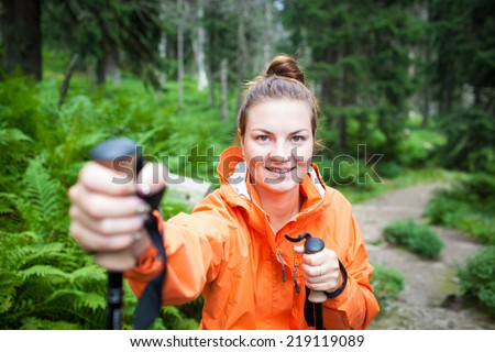 Active attractive young woman/female tourist nordic walking outdoors on a forest path, enjoying beauty of nature in national park (colorful image, shallow DOF) - stock photo