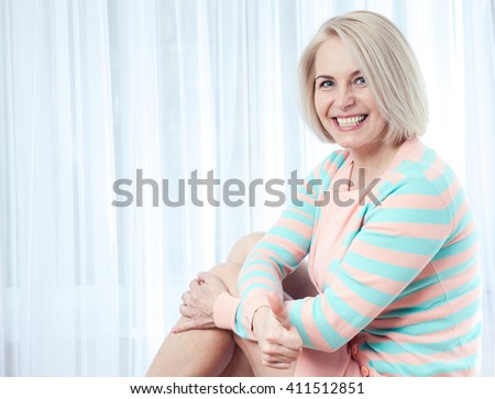 Active beautiful middle-aged woman smiling friendly and looking into the camera. Woman's face closeup. - stock photo
