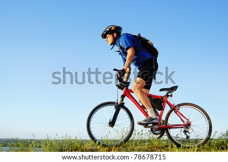 Active bicyclist riding at the countryside - stock photo