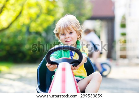 Active blond kid boy driving pedal toy car in summer garden, outdoors. His little brother on bike on background. Active leisure with children. - stock photo