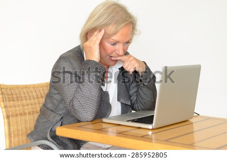 Active blond senior woman with formal clothes sitting thoughtful at a  desk in front of a silver laptop