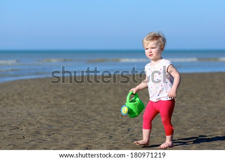 Active blonde little toddler girl in colorful outfit plays with watering can at a shore of the sea on a long calm peaceful beach on a warm sunny summer day