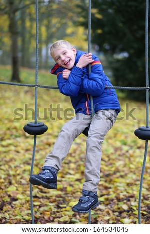 Active boy in warm blue coat having fun on the playground in the park on a sunny autumn day - stock photo