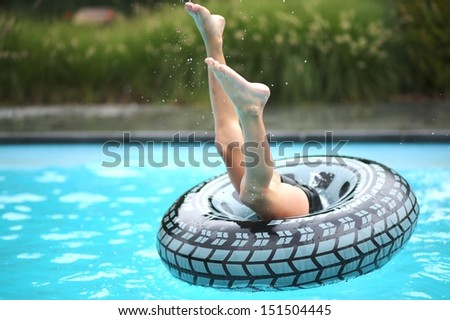 Active boy plays in outdoor swimming pool jumping inside inflatable ring  - stock photo