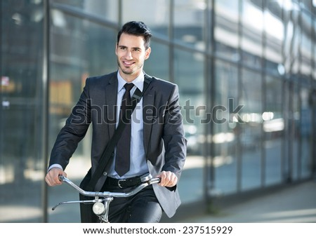 active businessman riding a bicycle on the way to job - stock photo