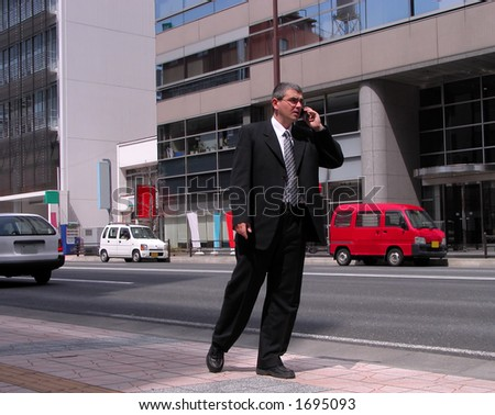 Active businessman using a mobile phone while he is walking in a city