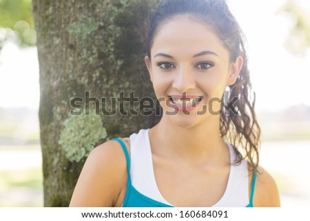 Active cheerful brunette looking at camera in a park on a sunny day