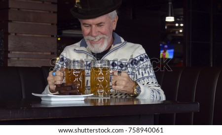 Active cheerful elderly men in a pub with a glass of beer
