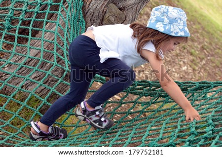 Active child (age 3 - 6 ) with a hat, climb on a net in the park. concept photo - stock photo