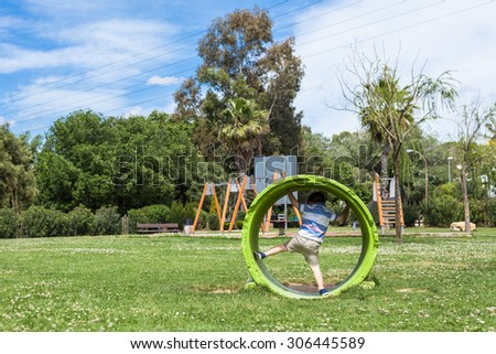 Active child boy playing in the park during sunny summer day. - stock photo
