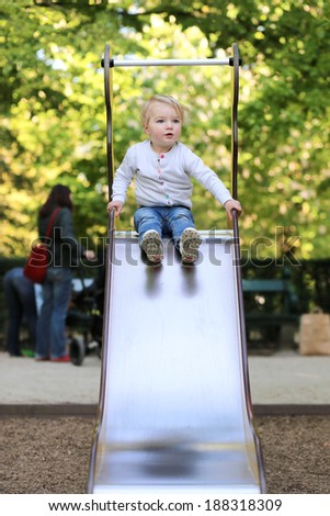Active child, curly blonde toddler girl having fun in playground on the slide on a sunny summer day - stock photo