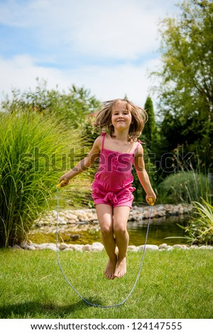 Active child - happy girl jumping with skipping rope outdoor in backyard - stock photo