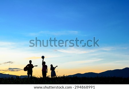 Active children spending time on summer meadow by sunset