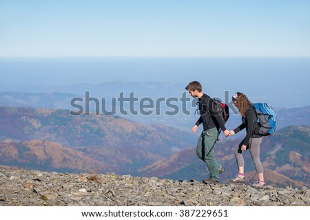 Active couple backpackers hiking with backpacks walking on the ridge of the mountain, open overview on the mountains on the background. Couple is holding hands. Sunny autumn day. Side view.