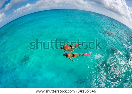 active couple snorkeling in turquoise waters on fun summer vacation - stock photo