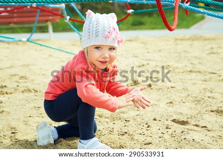 Active cute little girl on playground. child playing in the open air in the summer - stock photo