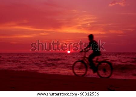 Active. Cyclist on the beach at sundown. - stock photo
