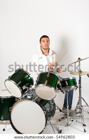 Active drummer playing at drums set in a studio - stock photo