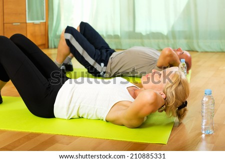 Active elderly couple training on mats at home - stock photo