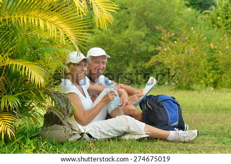 Active elderly couple with backpacks resting sitting on the grass - stock photo