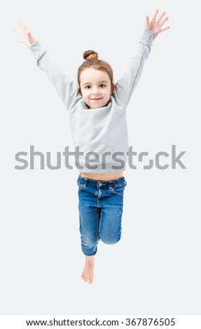 Active energetic child girl leaps. Neutral gray sweater and blue jeans. Gray background. Laid casual hair bun on top - stock photo