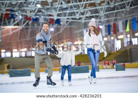 Active family at ice rink - stock photo